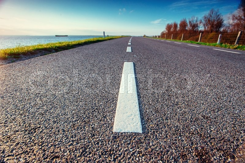 Asphalt road along the sea in a fantastic summer day in the sun, stock photo