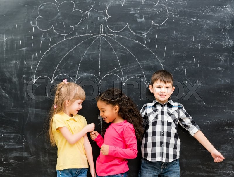 Three funny laughing children with umbrella drawn on the blackboard on backgorund, stock photo