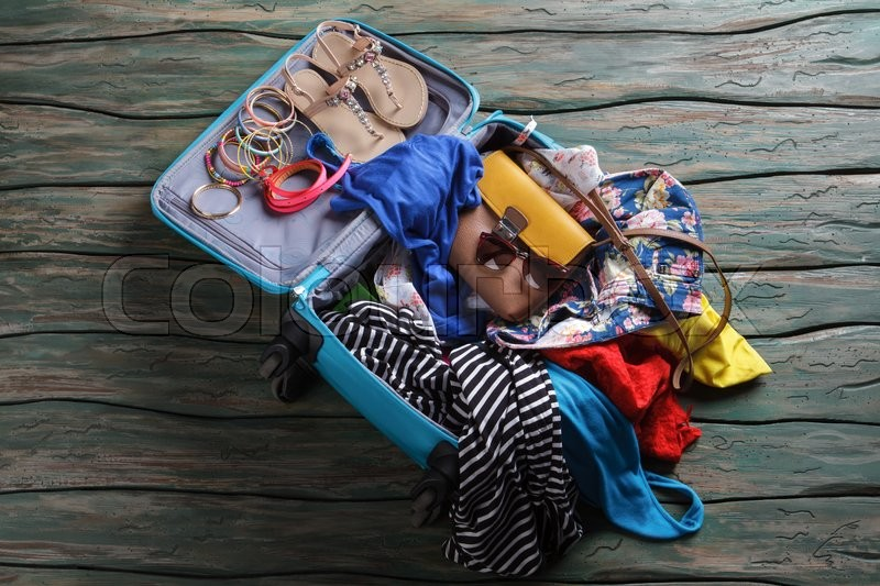 Stock image of 'Opened suitcase with crumpled clothes. Sandals and bracelets in luggage bag. Don't break the sunglasses. Ready to travel.'