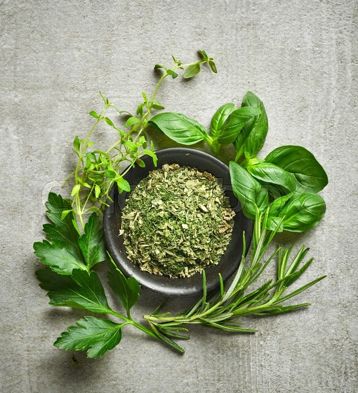 Bowl of dried herbs and fresh herbs on gray stone background, top view, stock photo