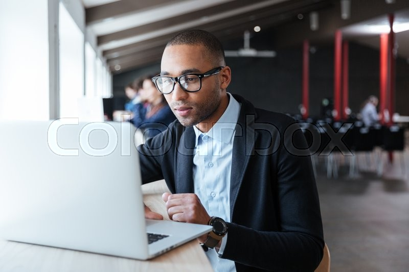 Young handsome businessman working with laptop in the office, stock photo