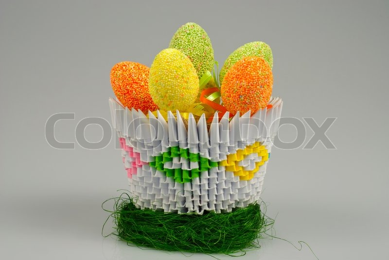Cute Easter Eggs On Decorative Grass In Origami Basket Isolated On