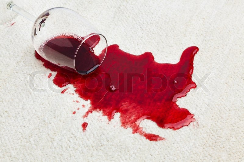 red wine is spilled on a carpet emptied the other glass stock
