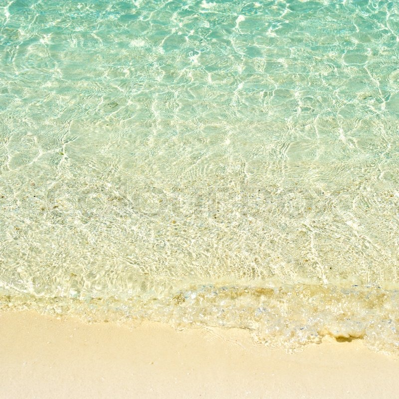 Wave on sandy tropical beach. turquoise water background