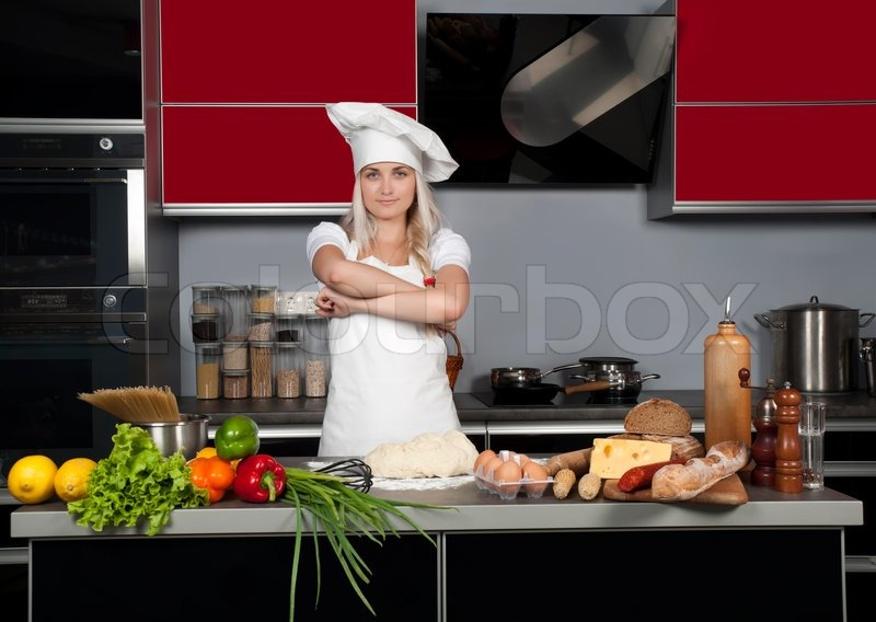 Young beautiful girl chef in the kitchen next to the kitchen table