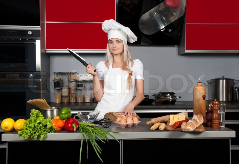 young beautiful girl chef in the kitchen with a knife in hand near the kitchen table with food. Black Bedroom Furniture Sets. Home Design Ideas
