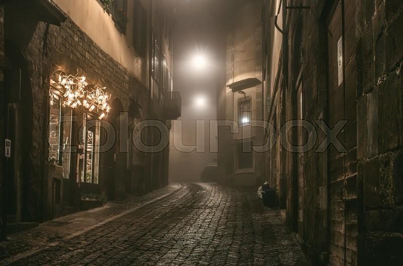 Old European narrow empty street of medieval town on a foggy evening. Taken in Bergamo, Citta Alta, Lombardia, stock photo
