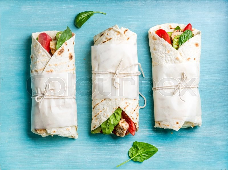 Healthy lunch snack. Tortilla wraps with grilled chicken fillet and fresh vegetables on blue painted wooden background. Top view, stock photo