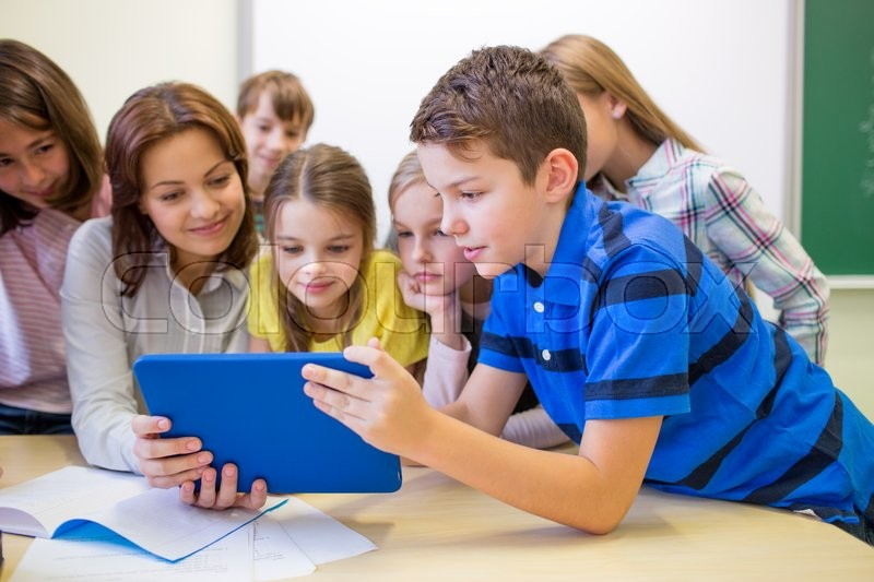 Education, elementary school, learning, technology and people concept - group of school kids with teacher looking to tablet pc computer in classroom, stock photo