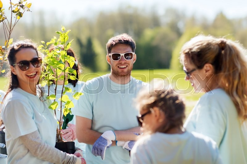 Volunteering, charity, people and ecology concept - group of volunteers planting trees in park, stock photo