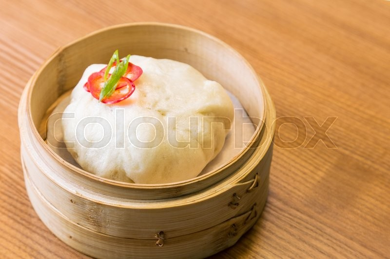 asian steam bun in a bamboo steamer a wooden table stock photo
