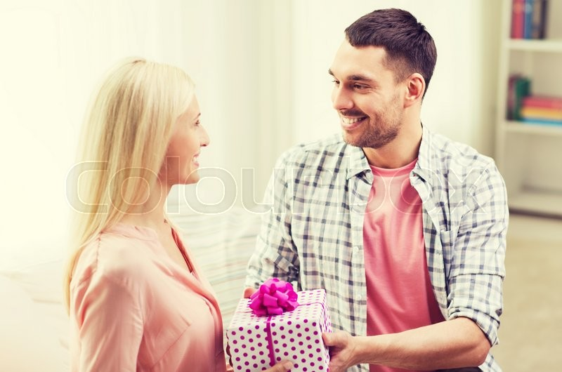 Relationships, love, people, birthday and holidays concept - happy man giving woman gift box at home, stock photo