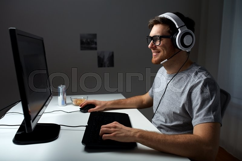 Technology, gaming, entertainment, let\'s play and people concept - happy young man in headset and glasses with pc computer playing game at home and streaming playthrough or walkthrough video, stock photo