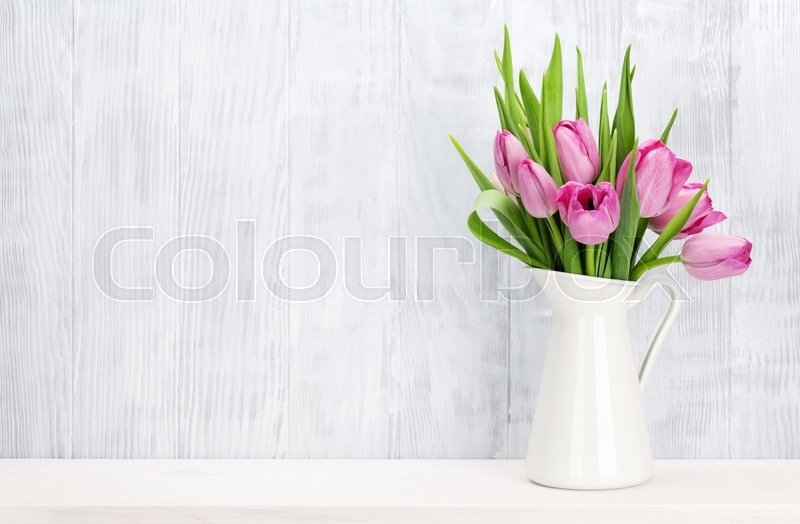 Fresh pink tulip flowers bouquet on shelf in front of wooden wall. View with copy space, stock photo