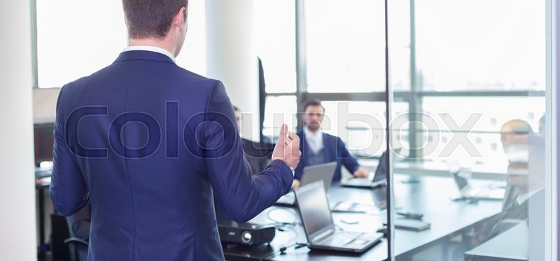 Business man making a presentation at office. Business executive delivering a presentation to his colleagues during meeting or in-house business training, explaining business plans to his employees. , stock photo