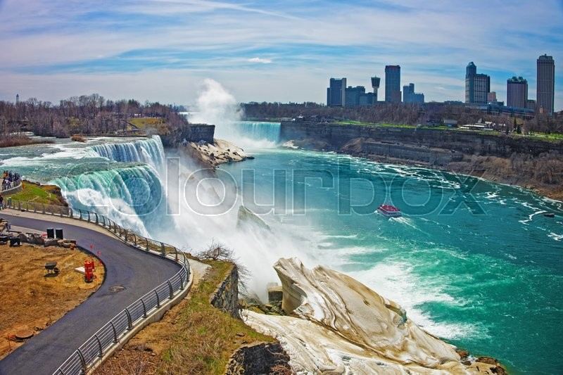 Stock image of 'Niagara Falls and a Ferry on Niagara River from the American side. A view on American Falls, Bridal Veil Falls, Goat Island, Horseshoe falls and Canada Skyscrapers on the background.'