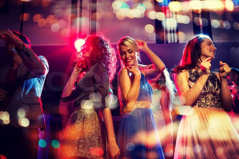 Party, holidays, celebration, nightlife and people concept - happy friends dancing in club with holidays lights, stock photo