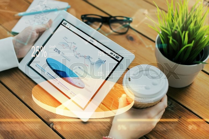 Stock image of 'business, statistics, technology, people and advertisement concept - close up of woman with charts on tablet pc computer screen and coffee cup on wooden table'