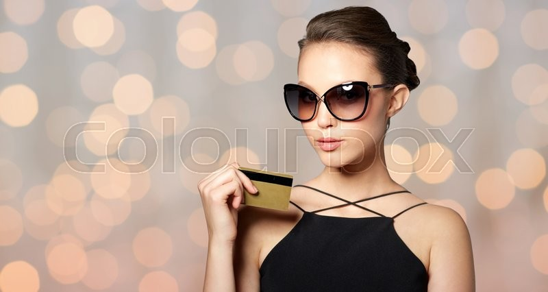 Stock image of 'shopping, finances, fashion, people and luxury concept - beautiful young woman in elegant black sunglasses with credit card over holidays lights background'