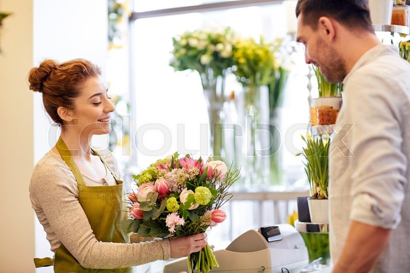 Stock image of 'people, shopping, sale, floristry and consumerism concept - happy smiling florist woman making bouquet for and man or customer at flower shop'