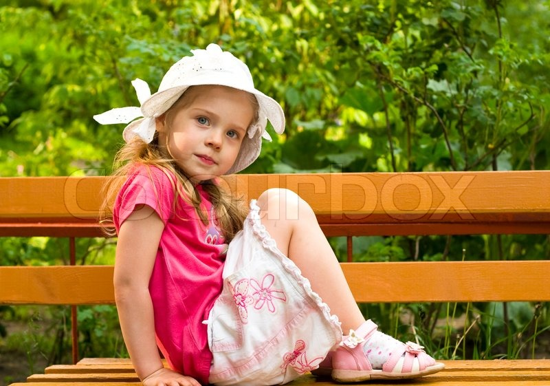 Stock image of 'Little girl sitting on the bench in park'