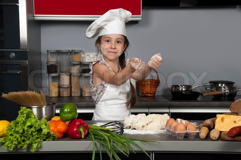 Kitchen Table With Food young beautiful girl chef in the kitchen next to the kitchen table