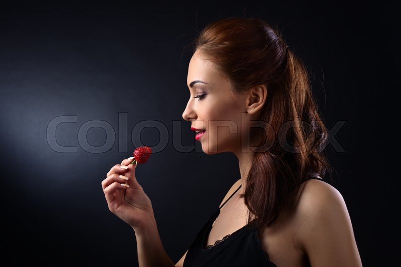 Stock image of 'young beautiful woman with strawberry on black background'