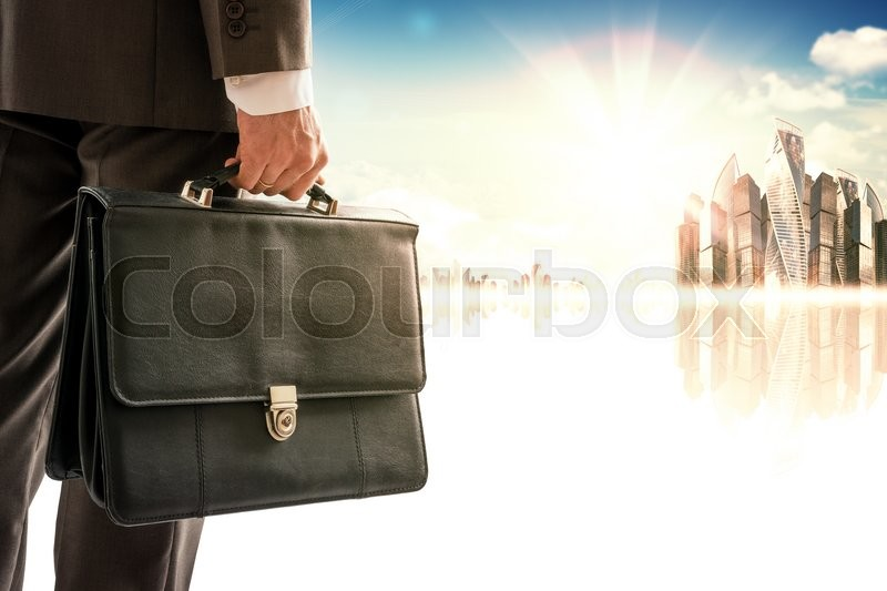 Stock image of 'Businessman with suitcase against modern city, rear view'
