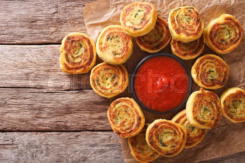 Stock image of 'sliced potato rolls with tomato sauce close up on the table. horizontal view from above\'