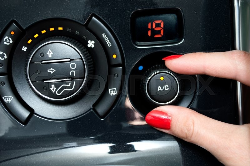 Woman turns on air conditioning in a car, stock photo