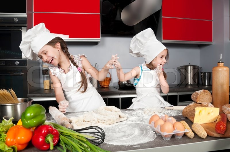 Two Little Girls Having Fun On The Kitchen Table With Raw