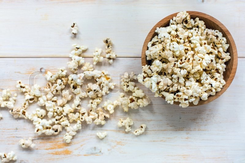 Stock image of 'Popcorn in bowl on a white wooden table.'