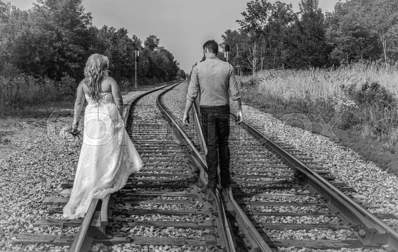 Stock image of 'Newlywed couple walking on the rails of a pair of railroad tracks in black and white.'