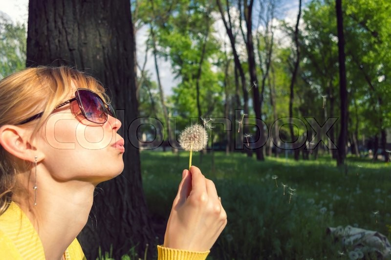 Stock image of 'leisure and recreation concept. Young woman blowing on a dandelion in the forest'