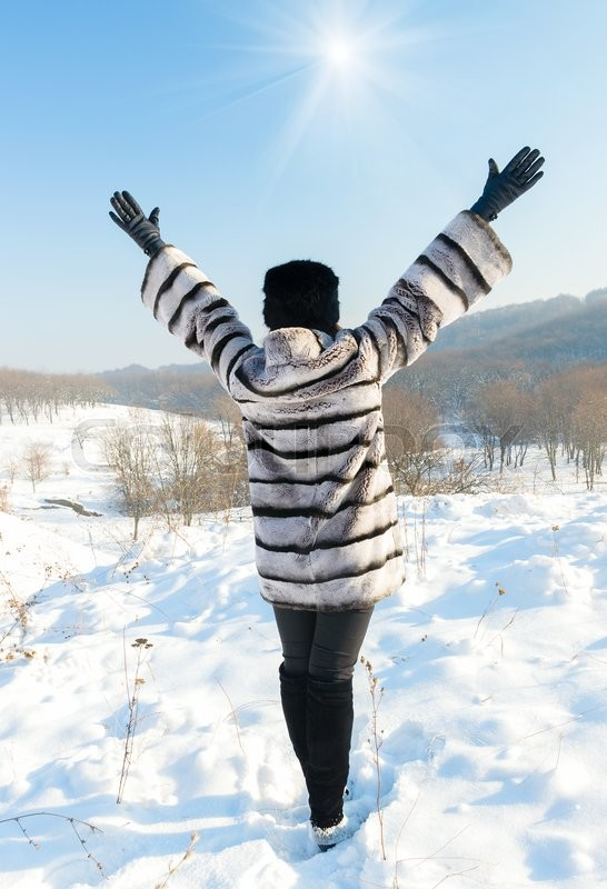 Stock image of 'Happiness emotions concept. Happy woman in a fur coat standing on top of a hill in winter'