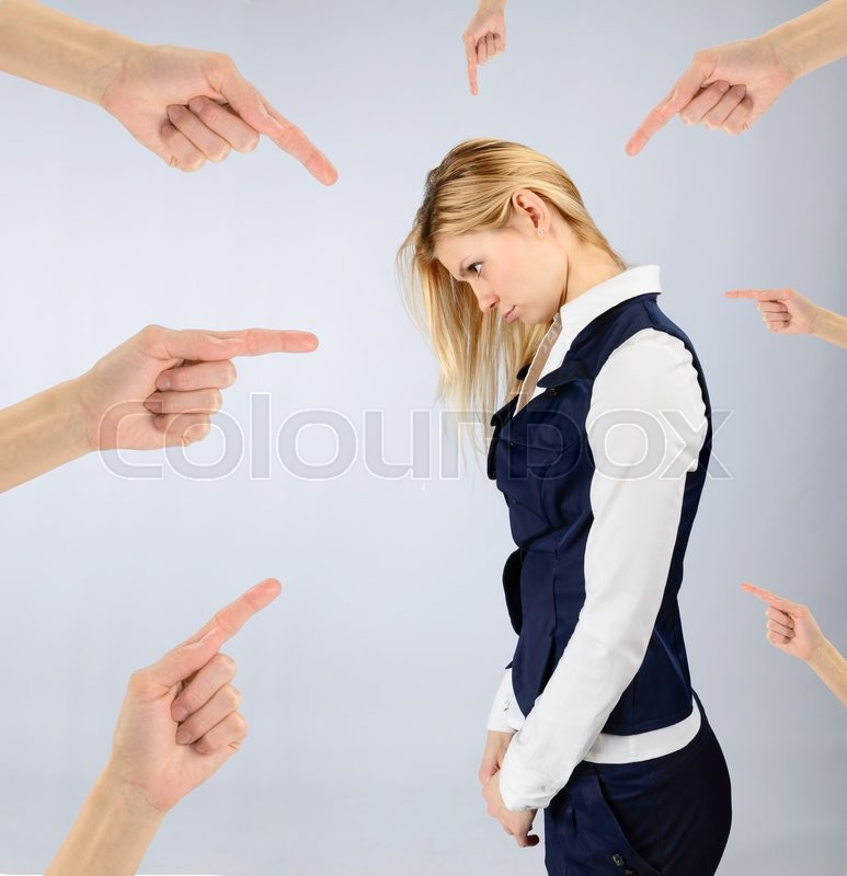 Stock image of 'Concept of blame and shame. Sad girl in a suit and hands pointing at it'