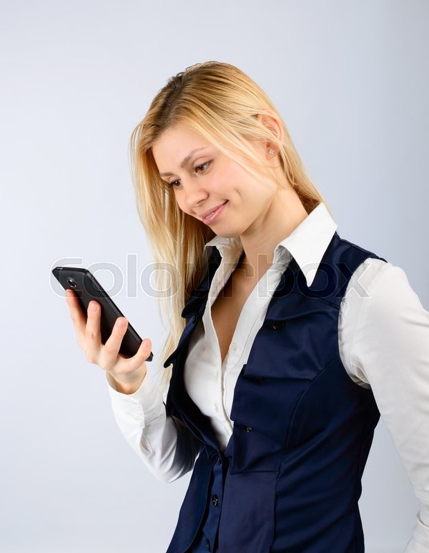 Stock image of 'Business woman holding a smartphone in his hand on a light background'