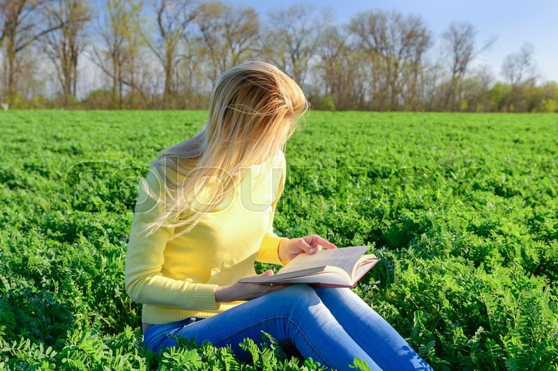 Stock image of 'Blond woman reading a book in a green field'