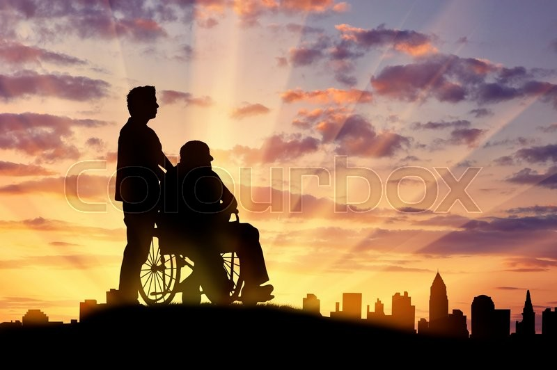 concept of disability and old age silhouette of a man looking after a disabled person on a background of city sunset stock photo colourbox