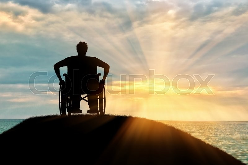 Stock image of 'Concept of disability and old age. Silhouette of disabled person in a wheelchair on a hill against a sunset sea'