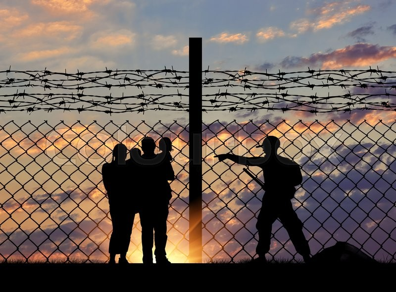 Stock image of 'The concept of security. Silhouette of a family with children of refugees and border guards and a fence with barbed wire on the background of evening city away'