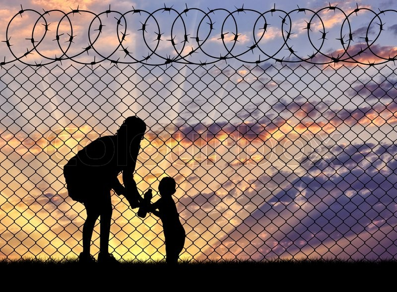 Stock image of 'Concept of the refugees. Silhouette mother with child refugees near the fence at sunset'