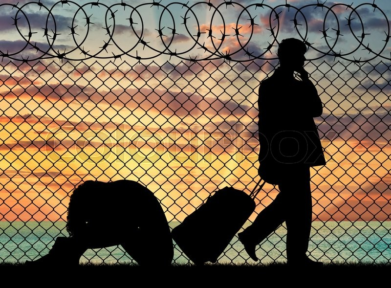 Stock image of 'Concept of the refugees. Silhouette of a couple of refugees near the border fence at sunset'