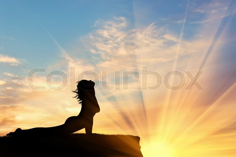 Stock image of 'Concept of meditation and relaxation. Silhouette of a girl practicing yoga exercise on the sunset background'