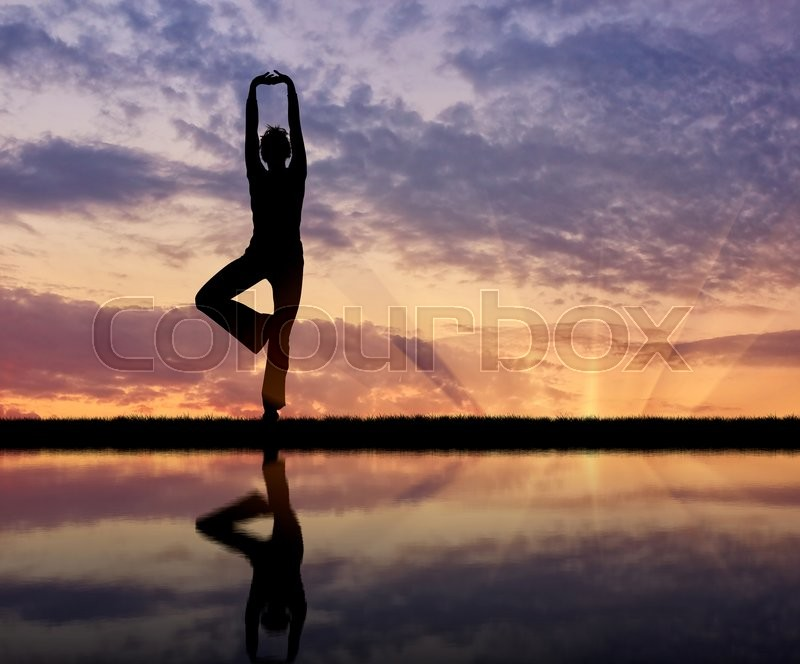 Stock image of 'Concept of meditation and relaxation. Silhouette of a girl practicing yoga at sunset and reflection in water'