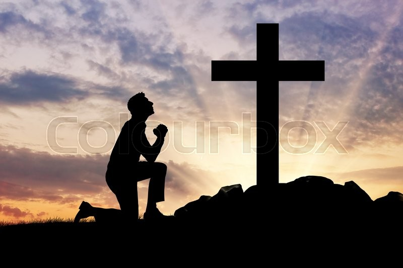 Concept of religion. Silhouette of a man praying before a cross at sunset, stock photo