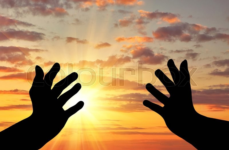 Concept of religion is a refugee. Silhouette of praying hands of an appeal to the sky, stock photo
