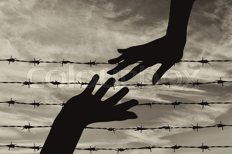 Stock image of 'Concept of refugee. Silhouette helping hand to refugees on the background of the fence of barbed wire'