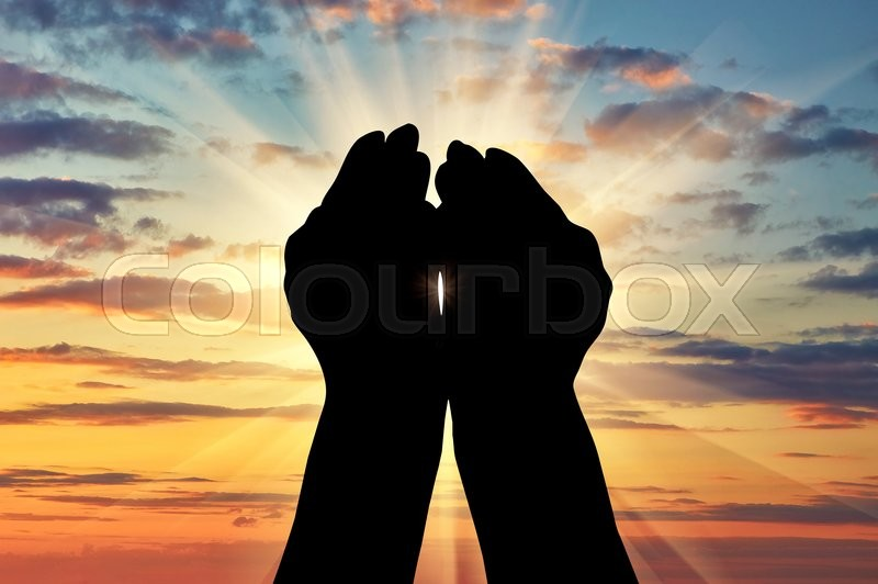 Stock image of 'Сoncept of Islam, the Koran. Silhouette of praying hands facing the sky at sunset'