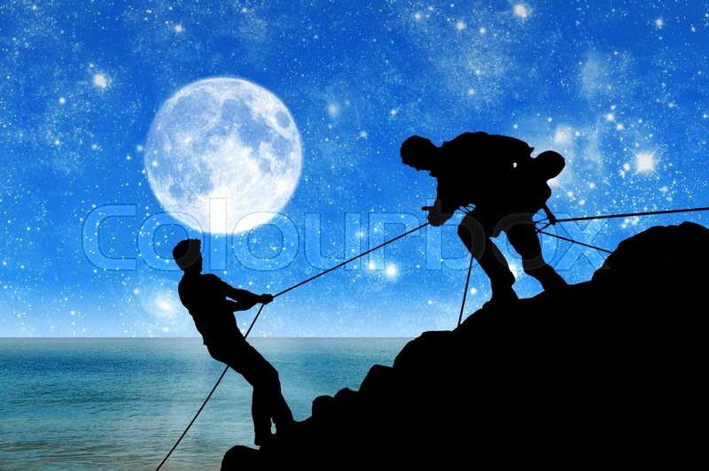 Stock image of 'Concept of aid. Silhouette of two climbers helping each other against the backdrop of the sea and the moon at night'